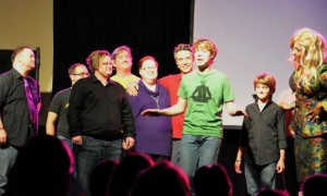 "Image of ""It Gets Better"" cast joined on stage by community chorus from Iowa City."